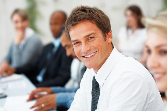 en smilende revisor sidder i forgrunden
