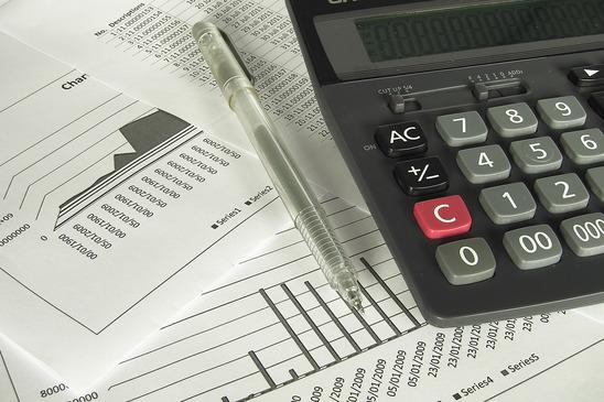 på et bord ligger der en lommeregner plus diverse finansielle papirer