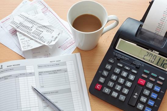 en bogholder er i gang med at lave et regnskab med papir, lommeregner og kaffe