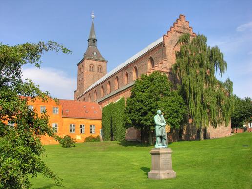 et billede af odense domkirke og en statue af hc andersen